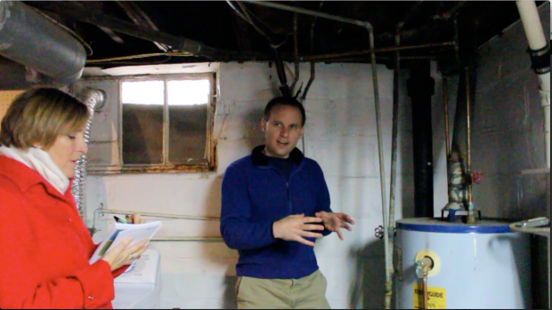 Dr. Whelton standing in a basement beside a hot water heater.