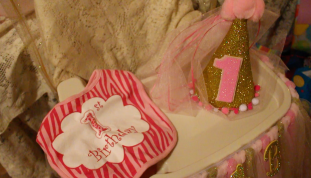 One-year birthday party hat and bib in pink and gold, sitting on a baby's high chair.